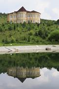 Cottage is reflected in the spring lake. Kennel Arboretum Blooming Valley - stock photo