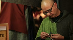 MURCIA, SPAIN-MARCH  Man making metal souvenir  in  a medieval market on Stock Footage