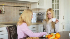 Two girls sit on a table in the kitchen talking and drinking tea Stock Footage