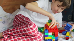 Boy in sleepwear playing constructor on the bed Stock Footage