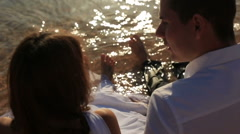 Wedding couple wet their feets in the sea close up Stock Footage