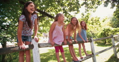 Little girls standing on a rustic wooden fence under tree - stock footage