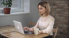 Woman working with laptop and dring coffee Stock Footage