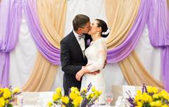 Bride And Groom Kissing At Wedding Reception - stock photo