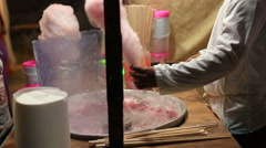 Cotton candy machine creates strands of sugar. Making pink cotton candy in a Stock Footage