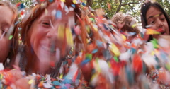 Children blowing colorful paper confetti outdoors in a park Stock Footage