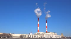 Old heat electric plant and smoke from stacks against blue sky. 4K video Stock Footage