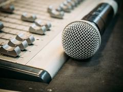 Selective focus microphone on the blur sound mixer background. Stock Photos