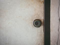 Doorknob on old wooden door and cracked wall - stock photo