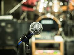 Selective focus on microphone with blurry music studio background - stock photo