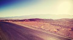 Vintage toned sunset over desert road, travel background Stock Photos