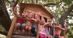Diverse group of children smiling and waving in a treehouse Stock Footage