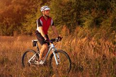 Man is riding a mountain bike in the field Stock Photos