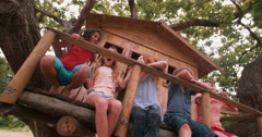 Childrentickling and laughing on the porch of a wooden treehouse Stock Footage