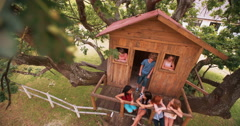 Children playing in a wooden treehouse in a grassy playground Stock Footage