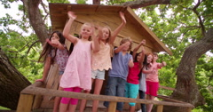 Mixed racial group of children waving from a wooden treehouse - stock footage