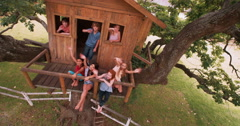 Group of children in a treehouse smiling and waving - stock footage