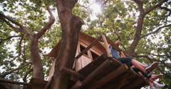 Three children talking while playing in a wooden treehouse - stock footage