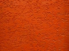 Red rough cement wall texture - stock photo