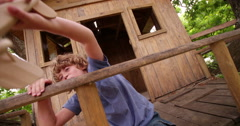 Boy sitting in a treehouse playing with toy wooden plane Stock Footage