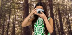 Composite image of asian woman taking picture with digital camera Kuvituskuvat