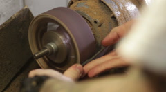Shoemaker repairing sole footwear in the grinder machine Stock Footage