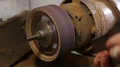Shoemaker repairing sole footwear in the grinder machine Stock Footage