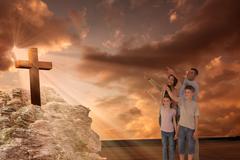 Family of four against cross religion symbol shape over sunset sky Stock Photos