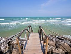 Wooden stair leading to the beach and the sea - stock photo