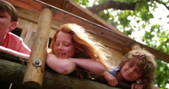 Children in a treehouse smiling together as friends - stock footage