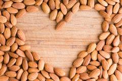 Heart shaped frame of fresh raw almonds Stock Photos
