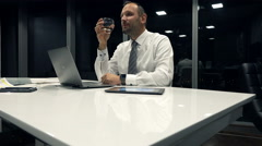 Young businessman relaxing and drinking alcohol in office during night, 4K - stock footage