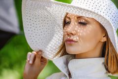 beautiful young woman in white hat - stock photo