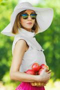 Stock Photo of portrait beautiful young woman serious hat holds basket apples