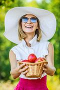 Woman wiht wicker basket holds red apples Stock Photos