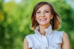 smiling beautiful young woman close-up - stock photo
