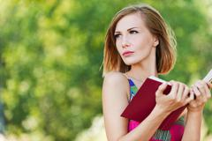 serious young beautiful woman holding red book - stock photo