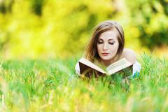 woman grass reading book - stock photo