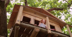 Children running out a treehouse and pointing - stock footage