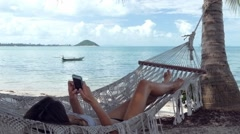 Relaxed woman using mobile phone in a hammock on the beach - stock footage
