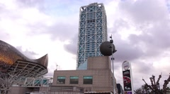 Tilt down from high tech tower to unusual sculpture and windy promenade Stock Footage
