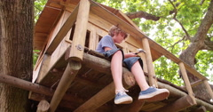 Boy repairing treehouse in big tree with bright green leaves - stock footage