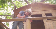Boy repairing his wooden treehouse with a hammer and nail Stock Footage