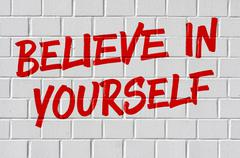 Graffiti on a brick wall - Believe in yourself Stock Photos