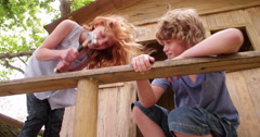 Childhood friends hammering and working to build their treehouse together - stock footage