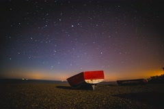 Astro Time Lapse - Lone Red Boat on a beach stars move across the sky - stock footage