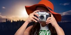 Composite image of woman with hat taking photograph with camera Kuvituskuvat