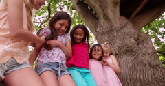 Mixed race group of little girls smiling together in park Stock Footage