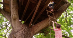 Children climbing up a rope ladder to their treehouse Stock Footage