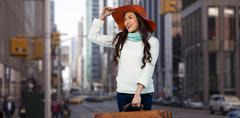 Composite image of smiling asian woman holding luggage holding hat - stock photo